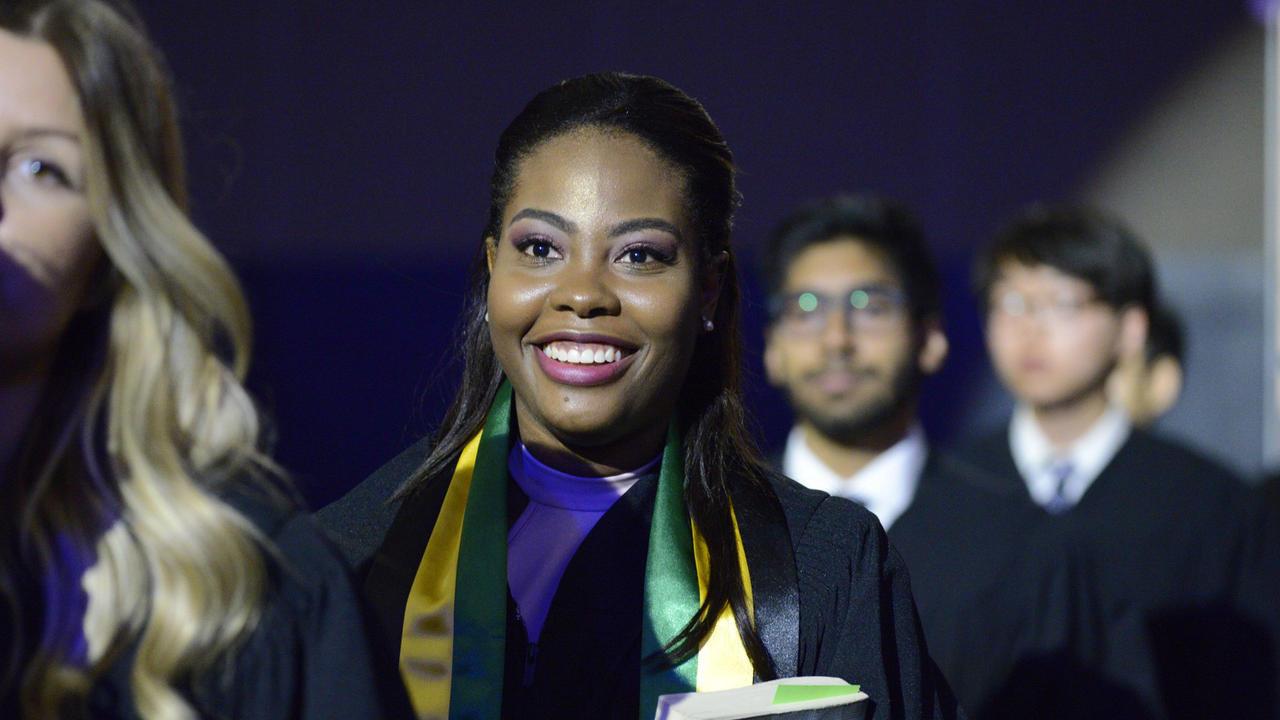 Students walk together at graduation.