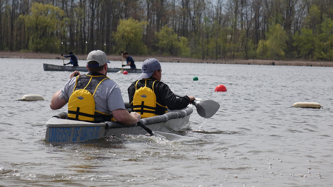 Two students paddling in a concrete canoe