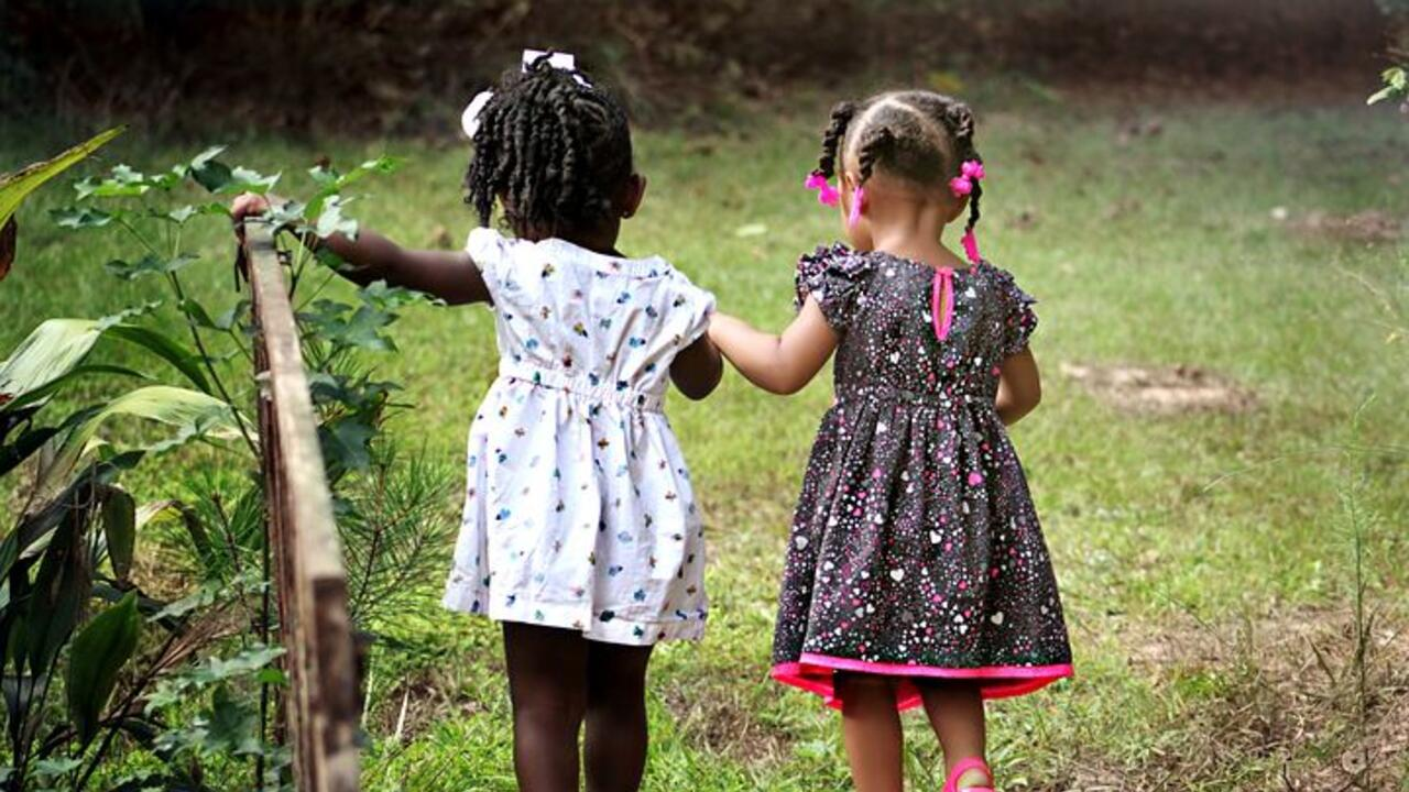two little girls walking together in nature