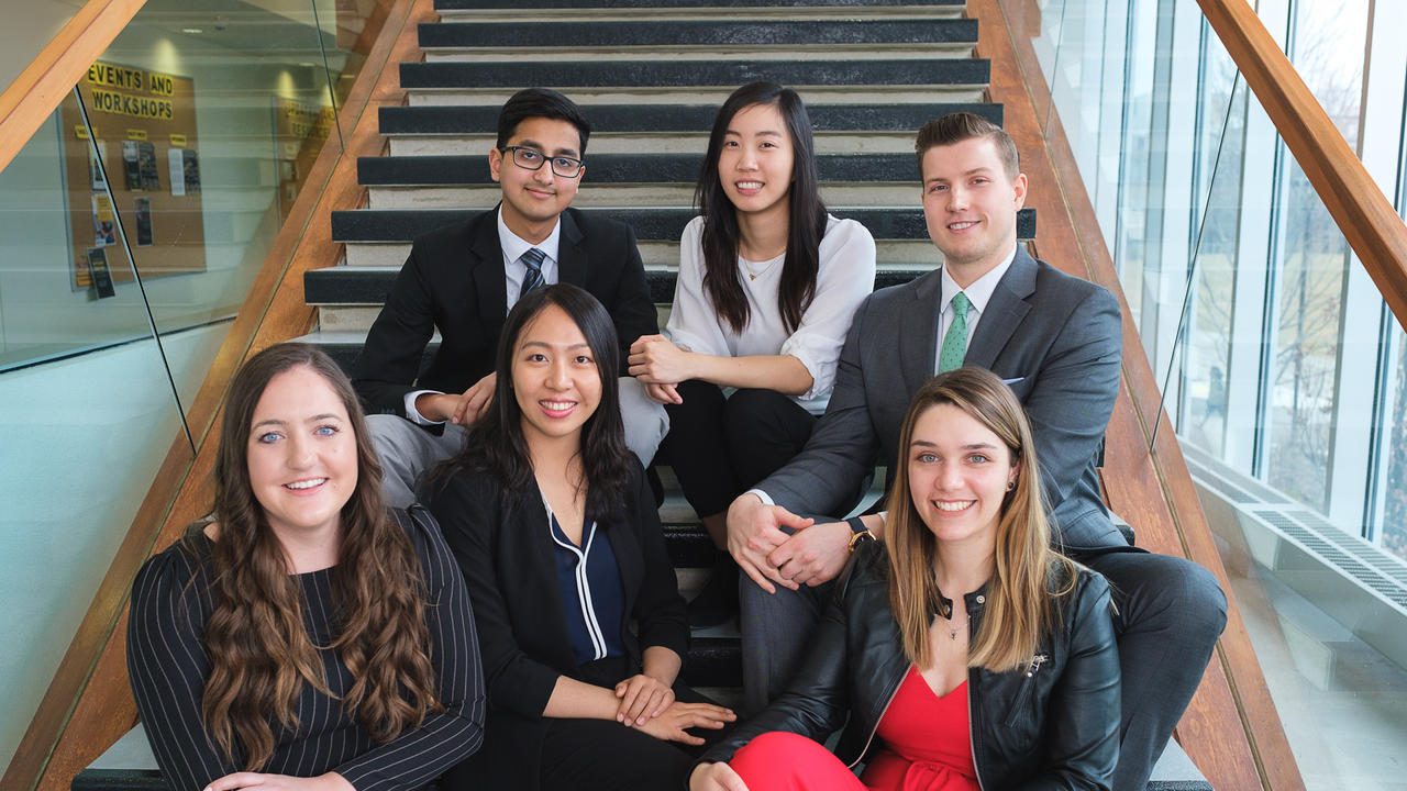 six students sitting on a staircase dressed in business attire