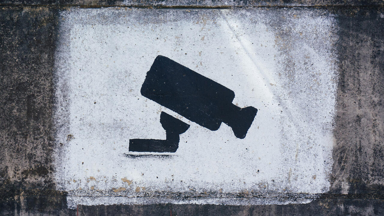 An illustration of a security camera spray painted on a wall