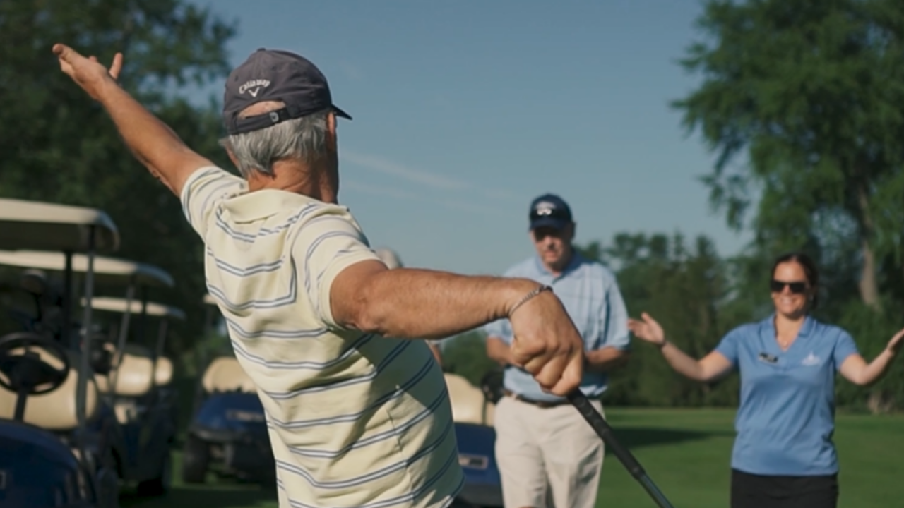 Older man celebrating with others on a golf course