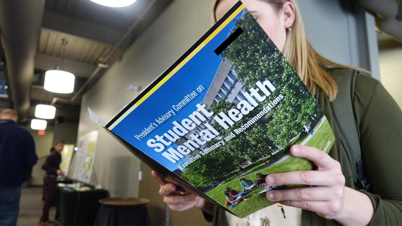 Student holding a Student mental health handbook