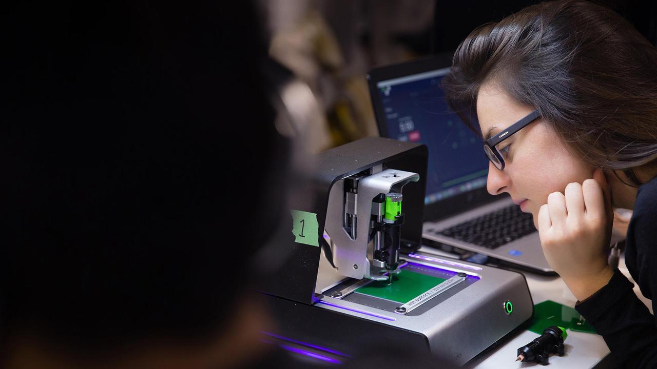 Girl watching as a circuit board is printed