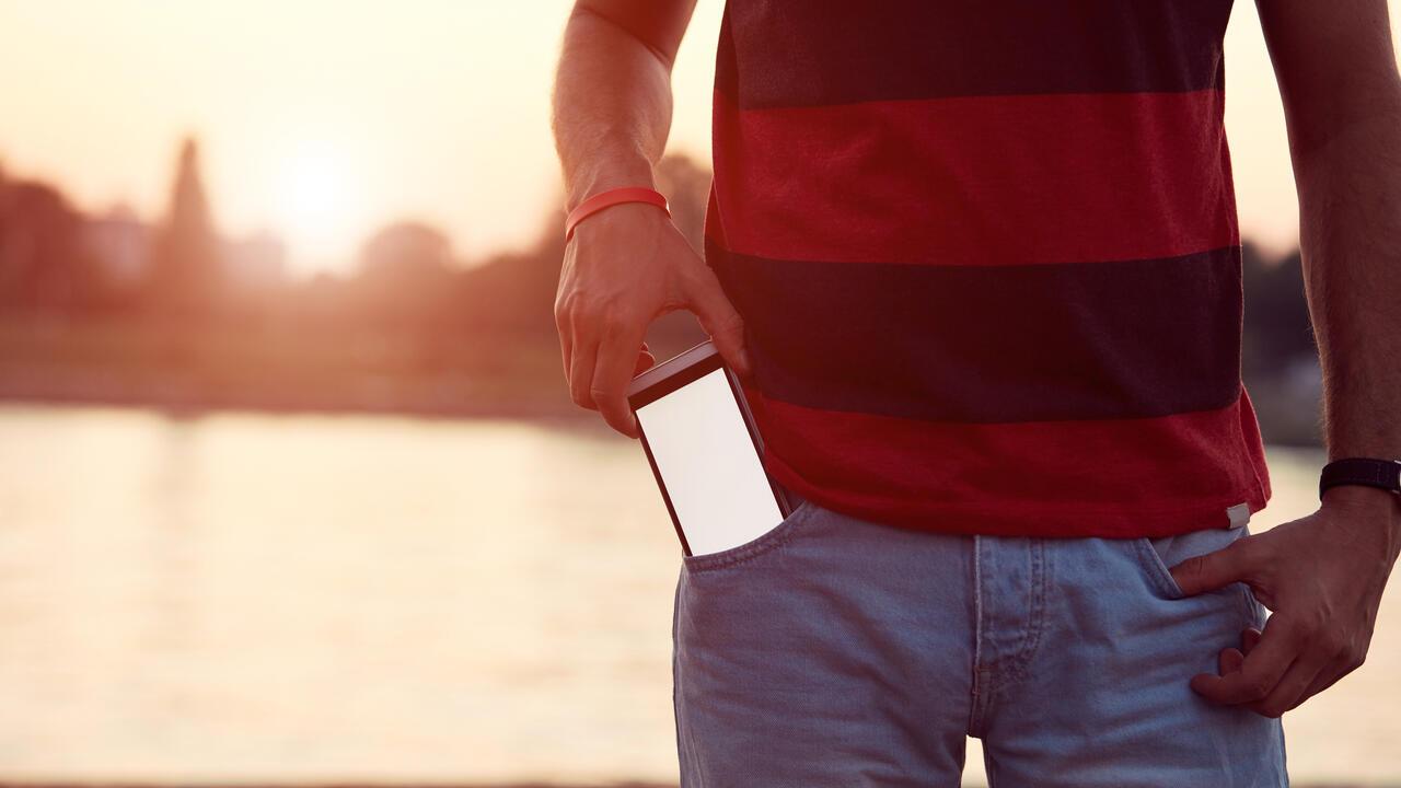 Man holding cellphone in pocket near river.