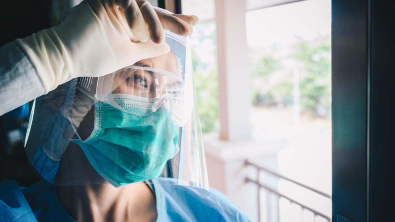 A nurse wearing a face mask looks through a window
