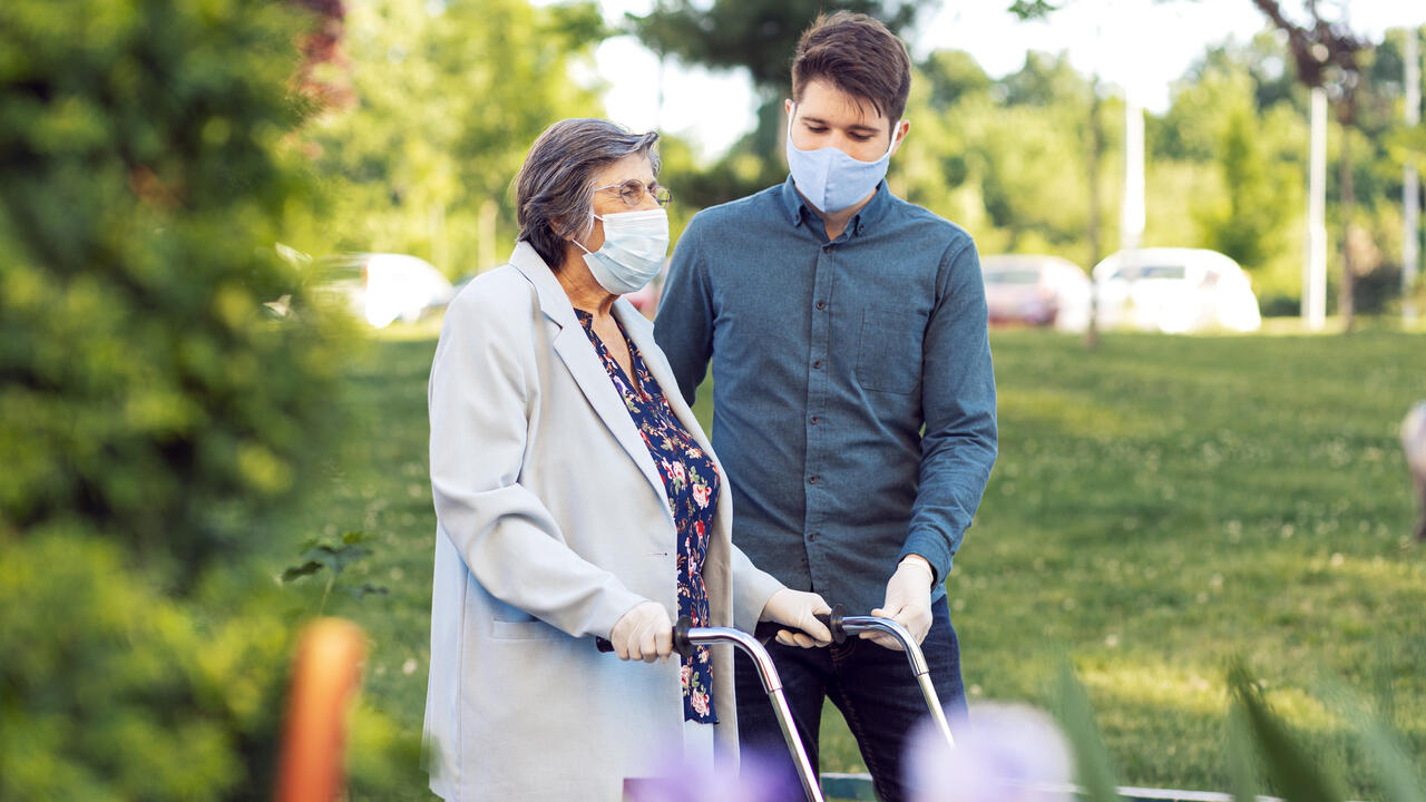 Young man helping senior woman walking in the street