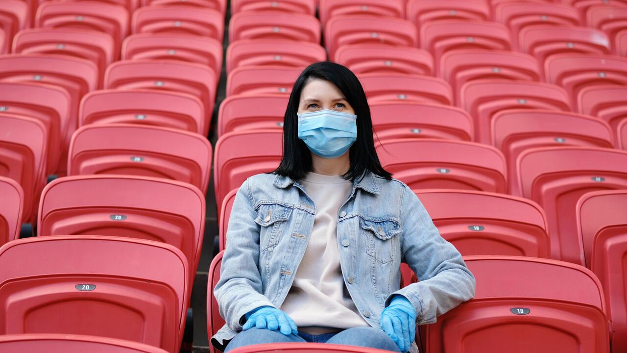 Woman in mask sitting in bleachers
