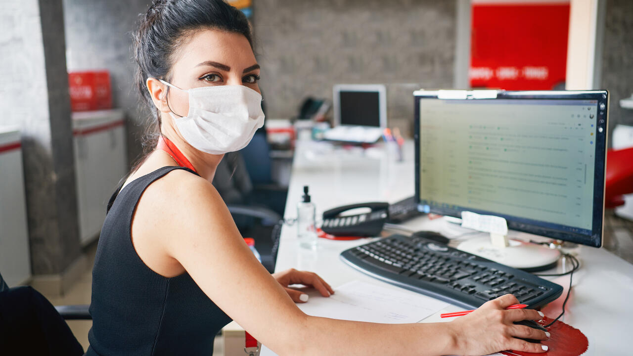 Woman wearing face mask in the office during COVID-19 pandemic