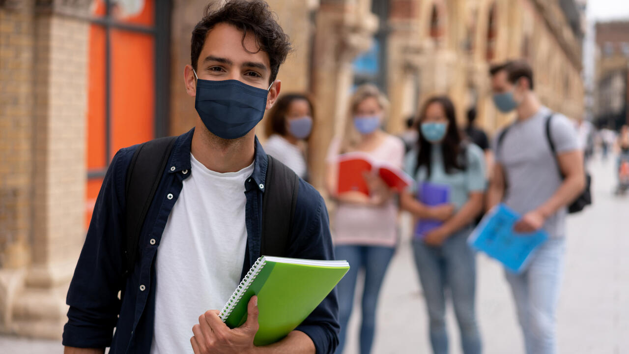A student wearing a face mask and holding a book with other students in the background