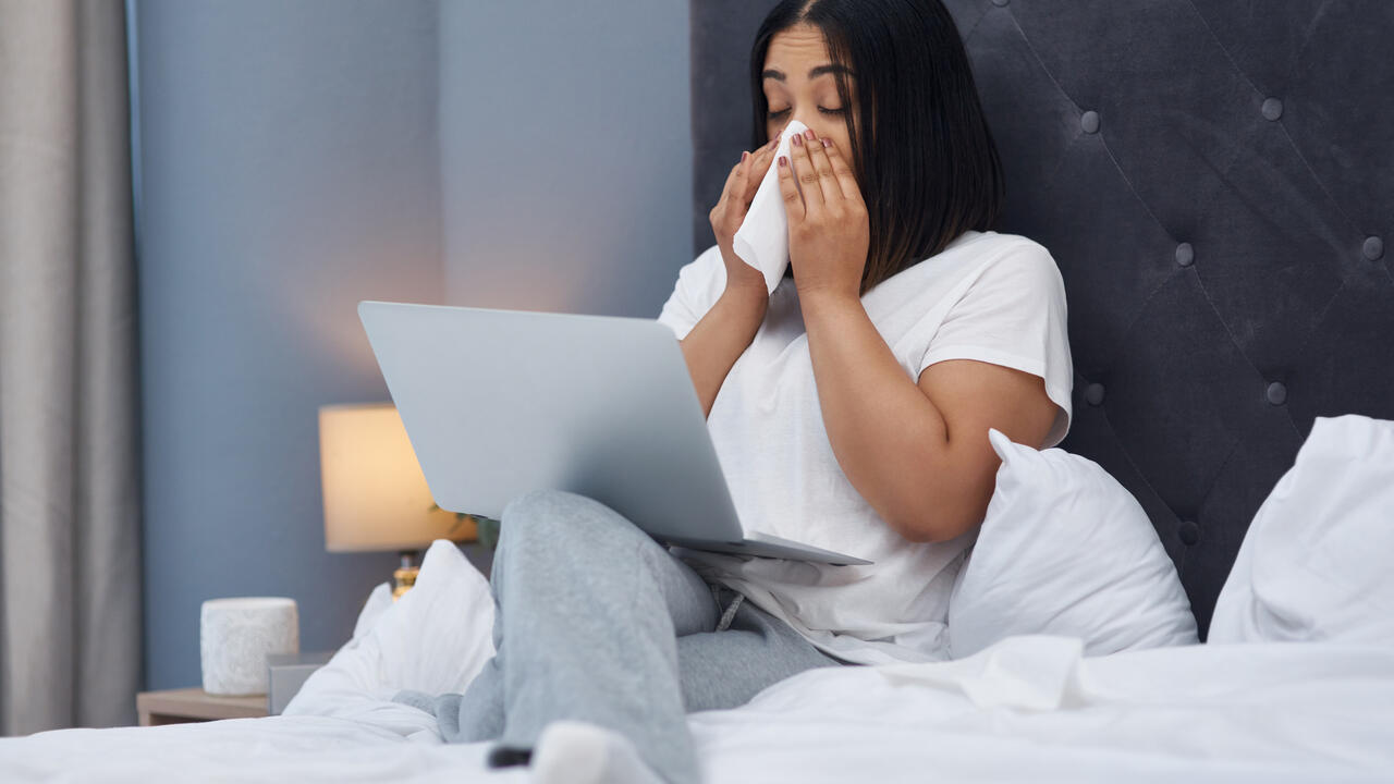 A woman sick in bed at home with a laptop