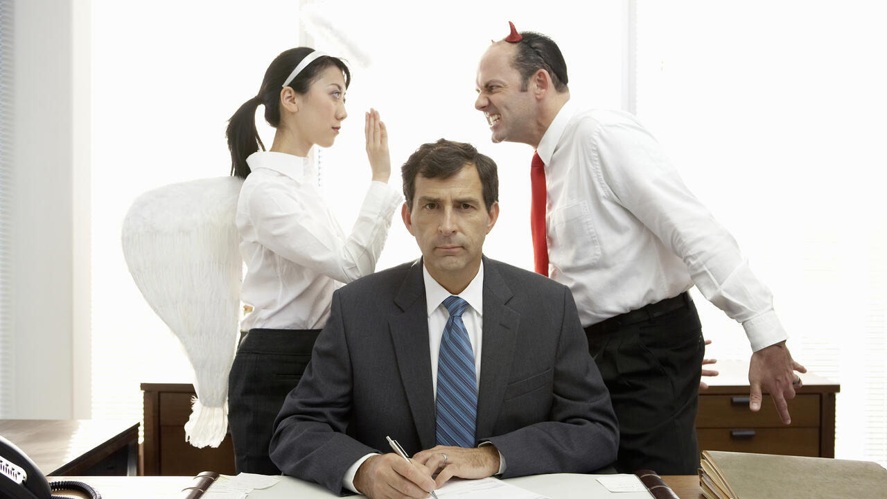 Executives with halo and devil horns standing behind businessman