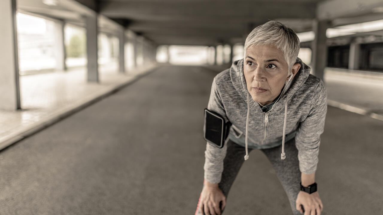 Portrait of a woman fighting breast cancer, resting after jogging.