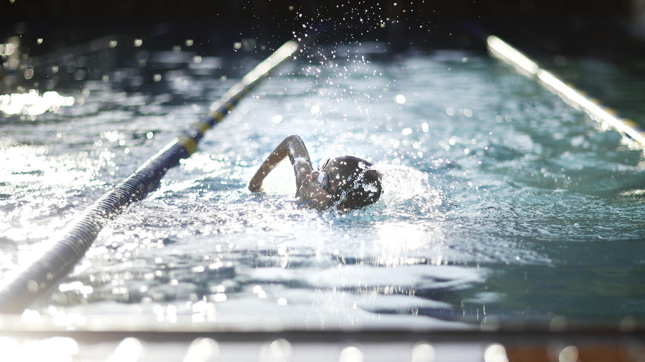 Child competing in swimming race in pool