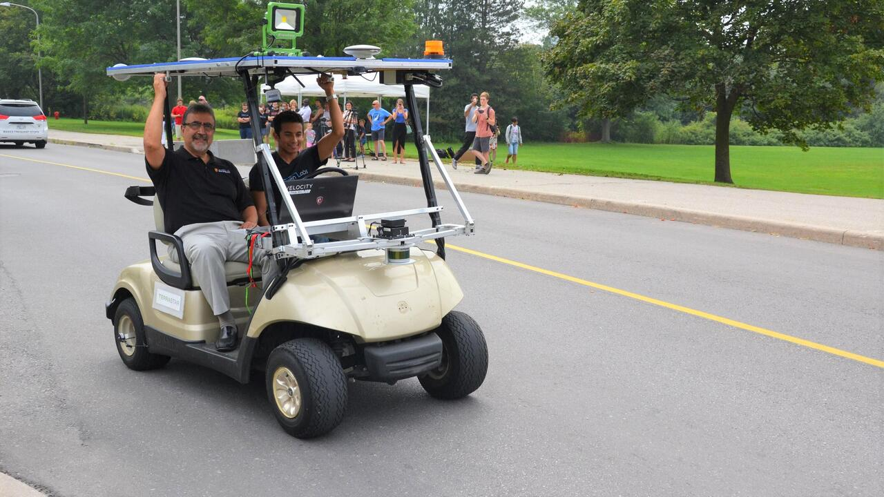 Feridun Hamdullahpur and Alex Rodrigues in a self-driving golf cart during testing in 2015 at the University of Waterloo.