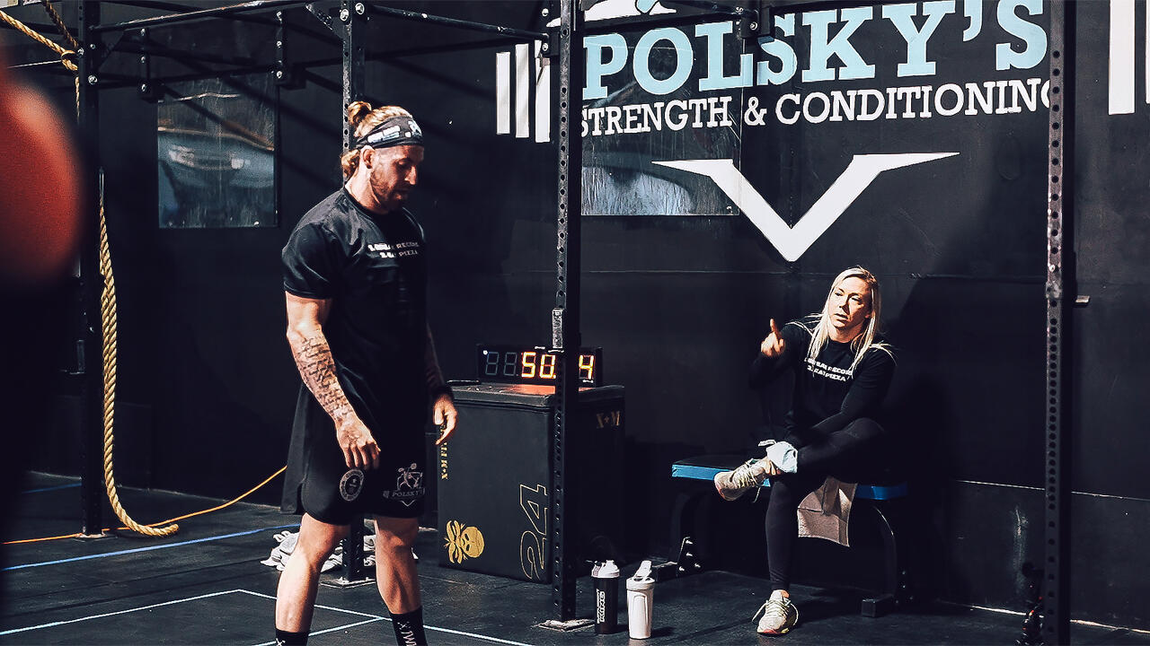Nick Anapolsky looks at a gym floor while a blond woman looks on