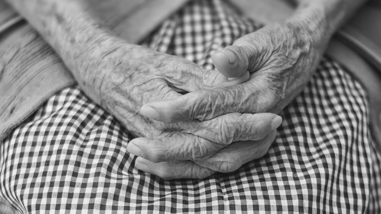 Clasped hands resting on lap
