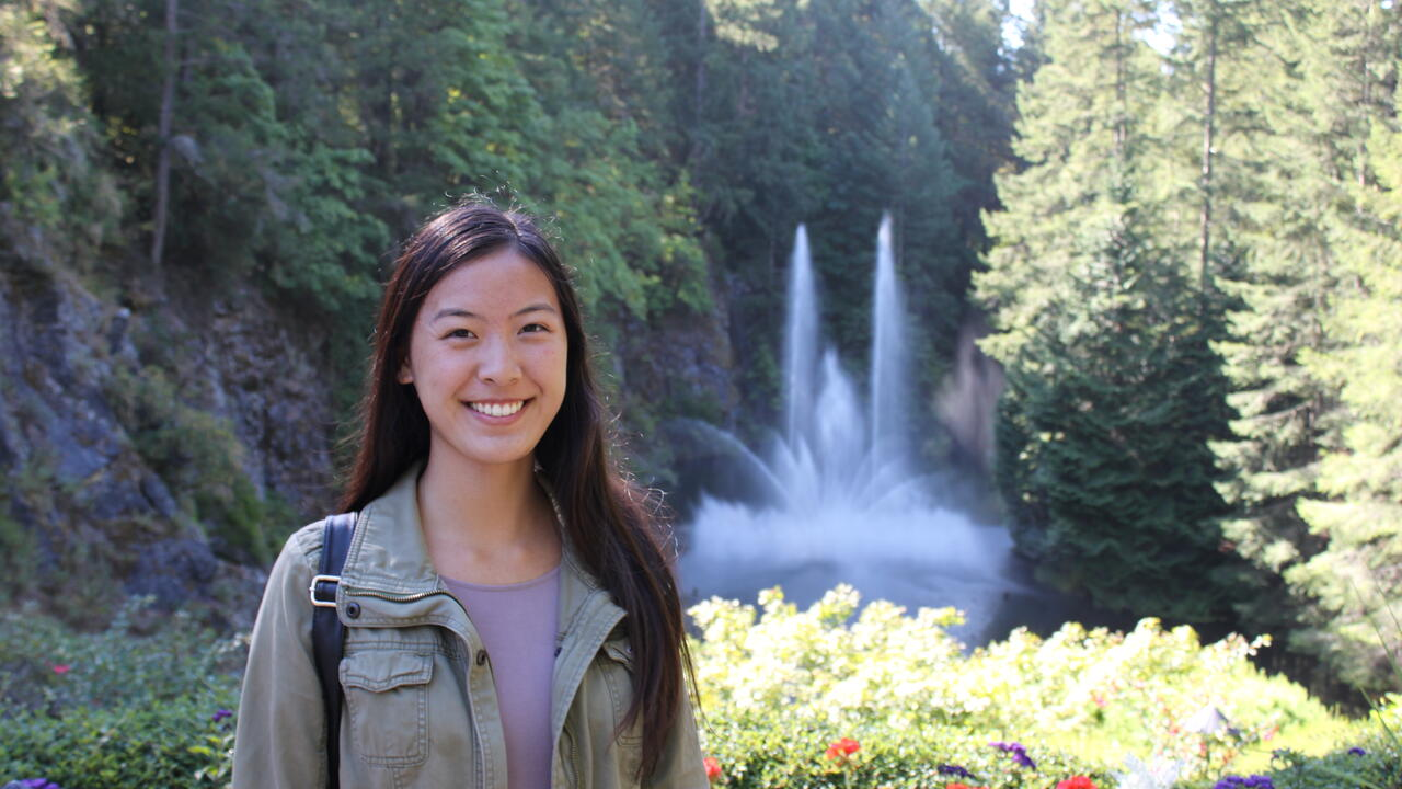Kinesiology graduand Tina Jiao in front of a garden