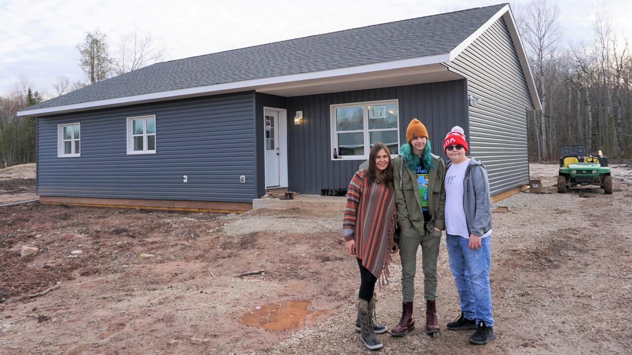 Melissa Millette (left to right) with two of her children, Riley and Reichal, pose outside their new house.