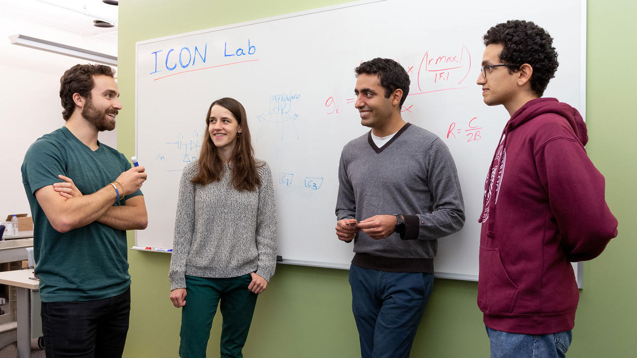 Professor Omid Abari and his students stand beside a white board