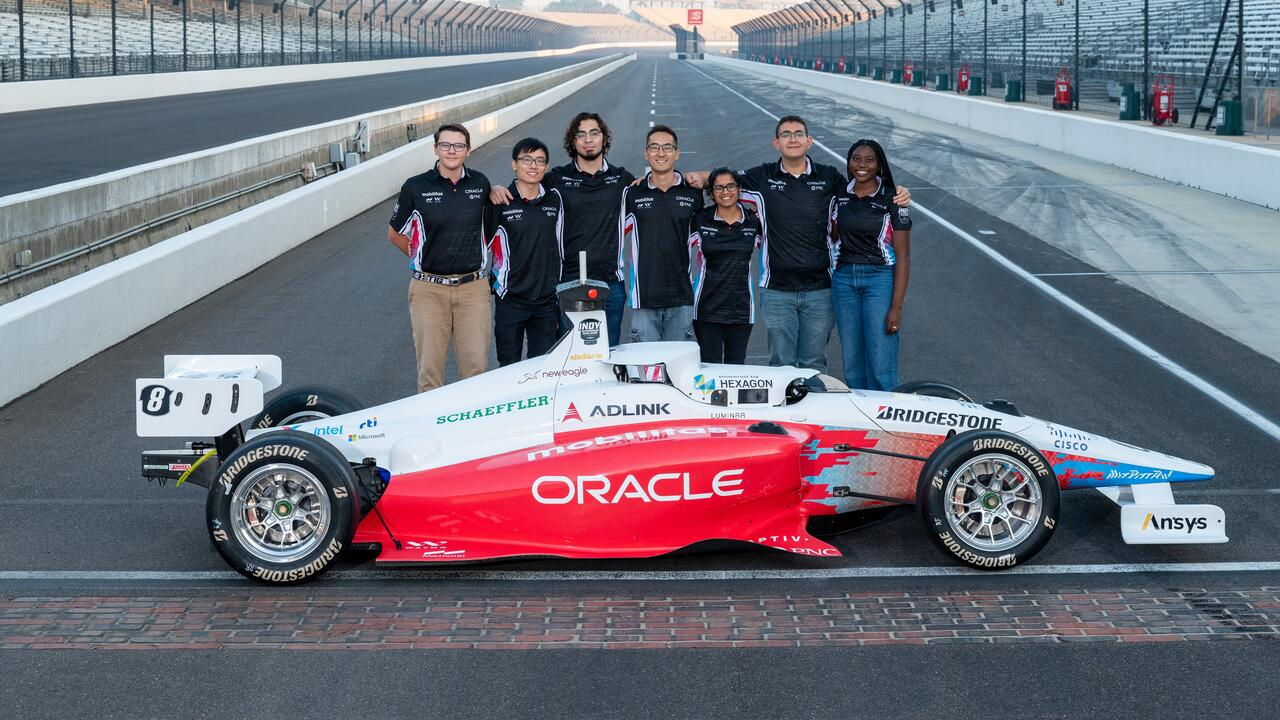 Members of team with their car at Indy Autonomous Challenge.