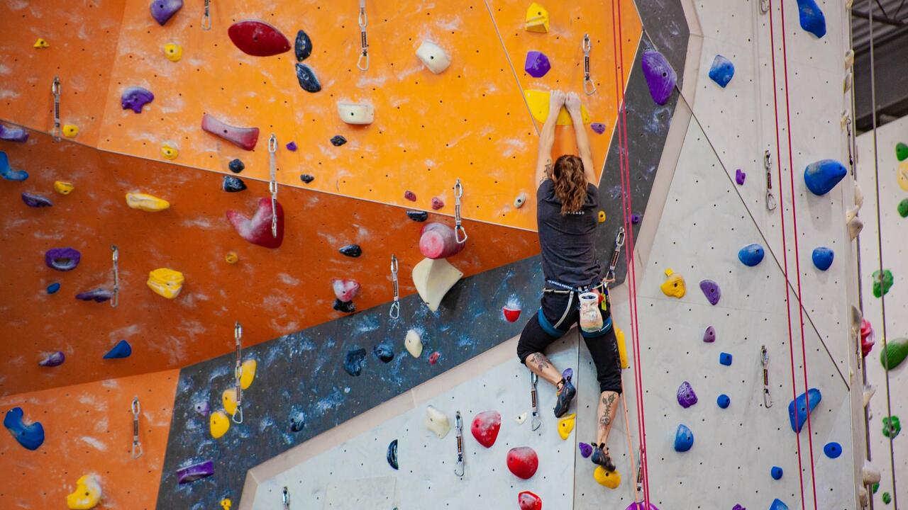 A climber using an indoor rock climbing wall.