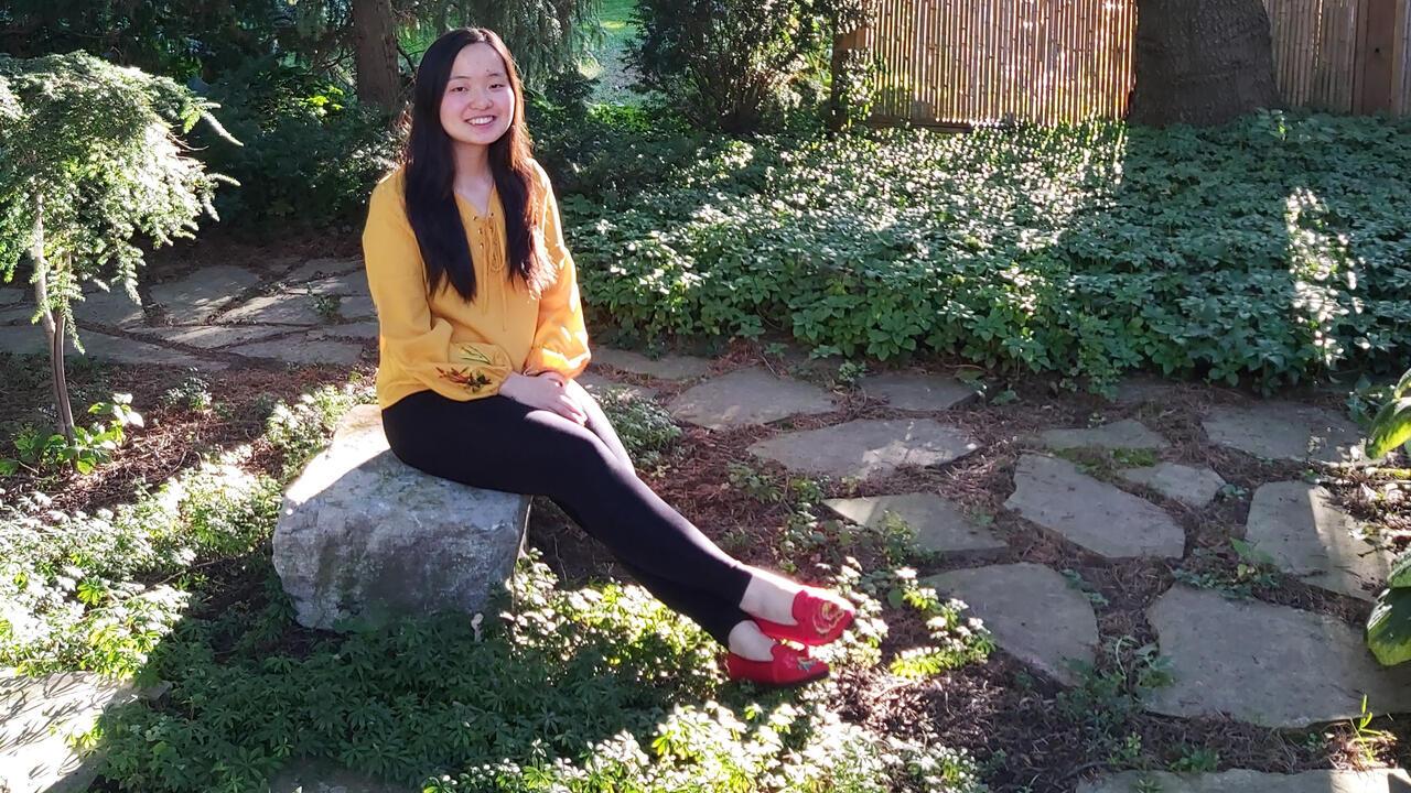 Maggie Chang sitting in a garden