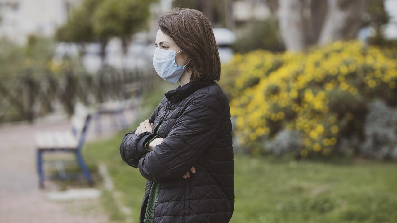 Woman with folded arms wearing a COVID-19 mask.