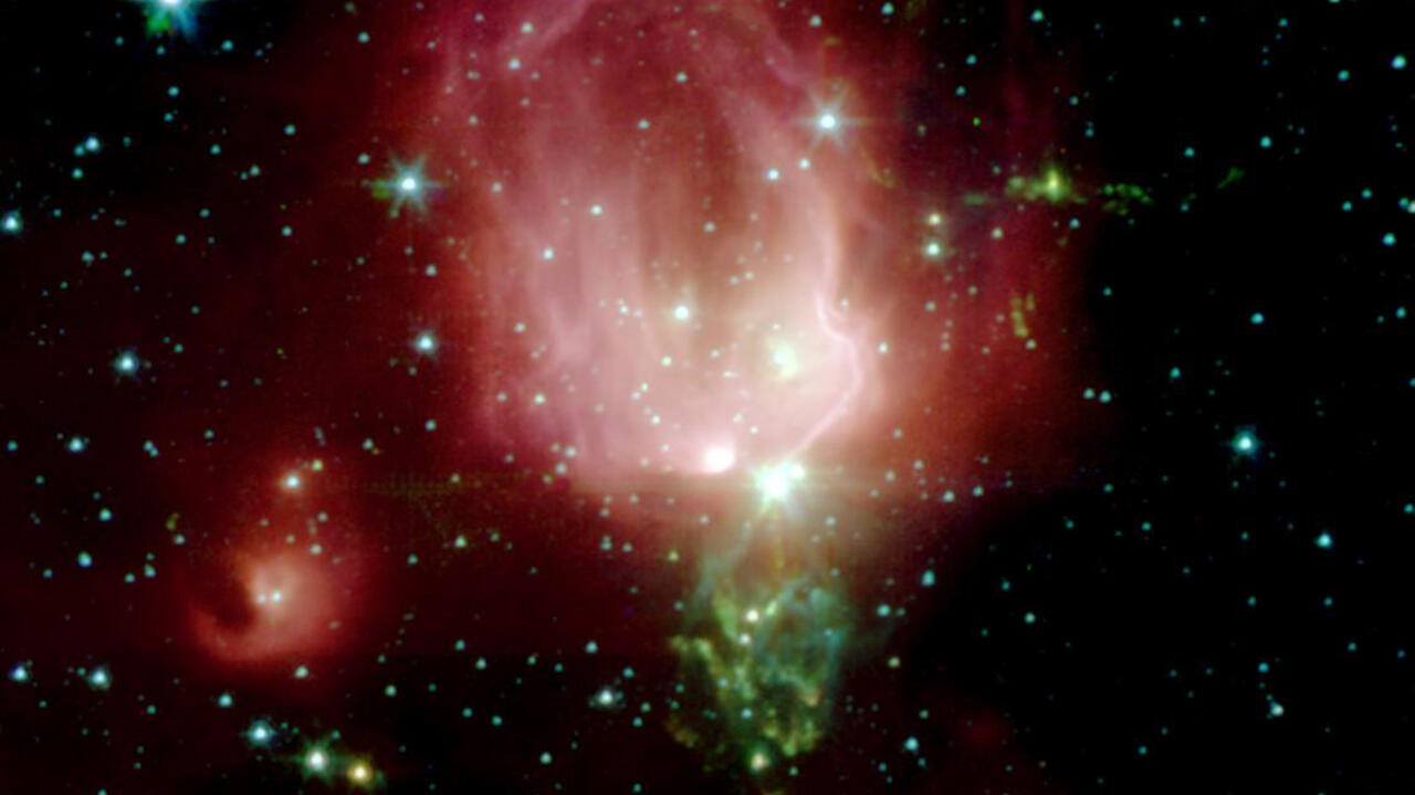 Star Forming region NGC_7129, a cloud of pink and green gas with balls of bright light inside. Stars around the outside