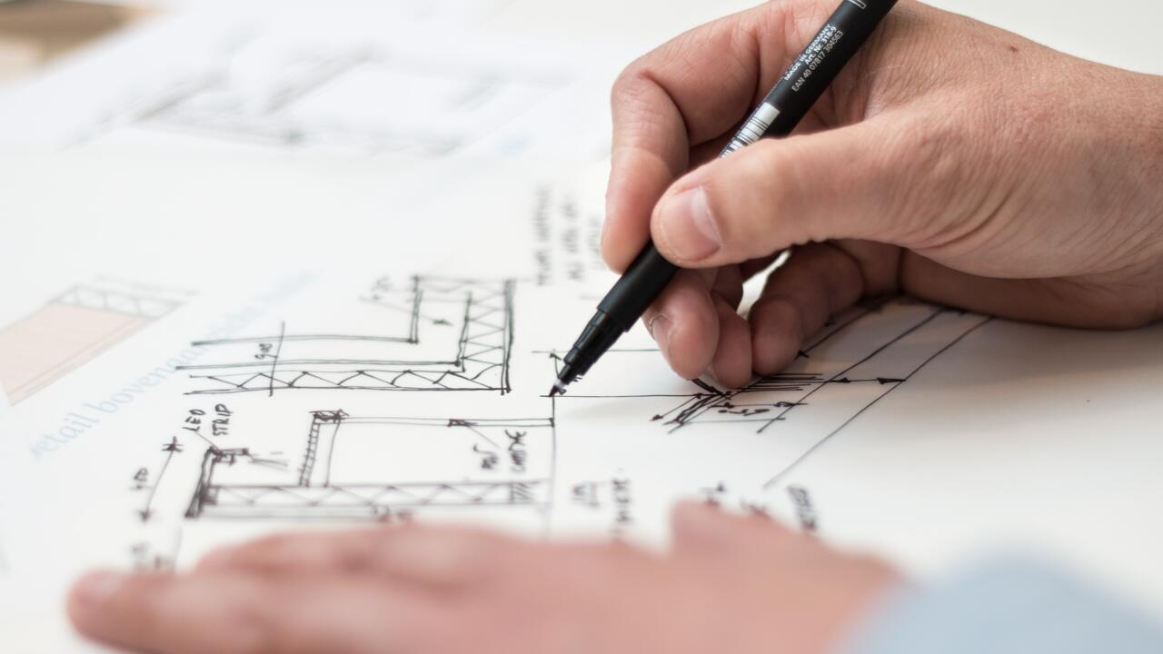person holding a black pen and designing on paper
