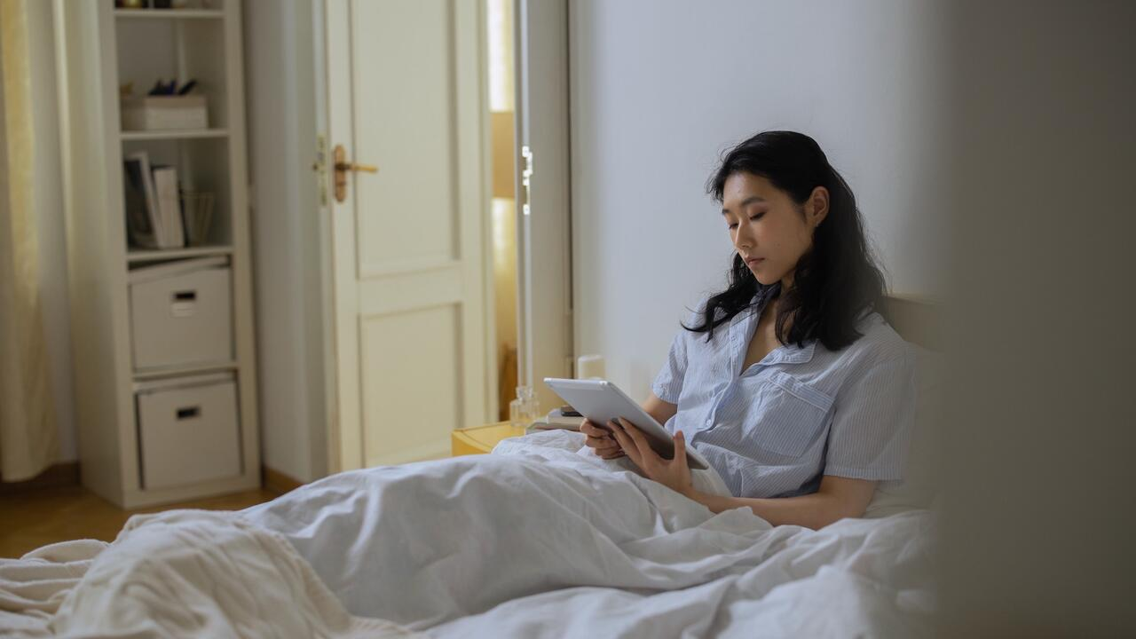 A female lying in bed with a tablet looking at a tablet