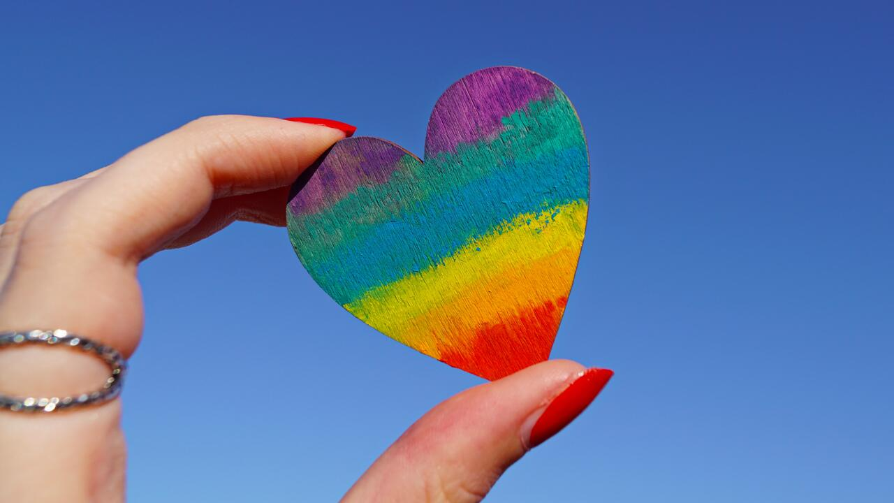 hand holding heart shaped wood peice with rainbow colours