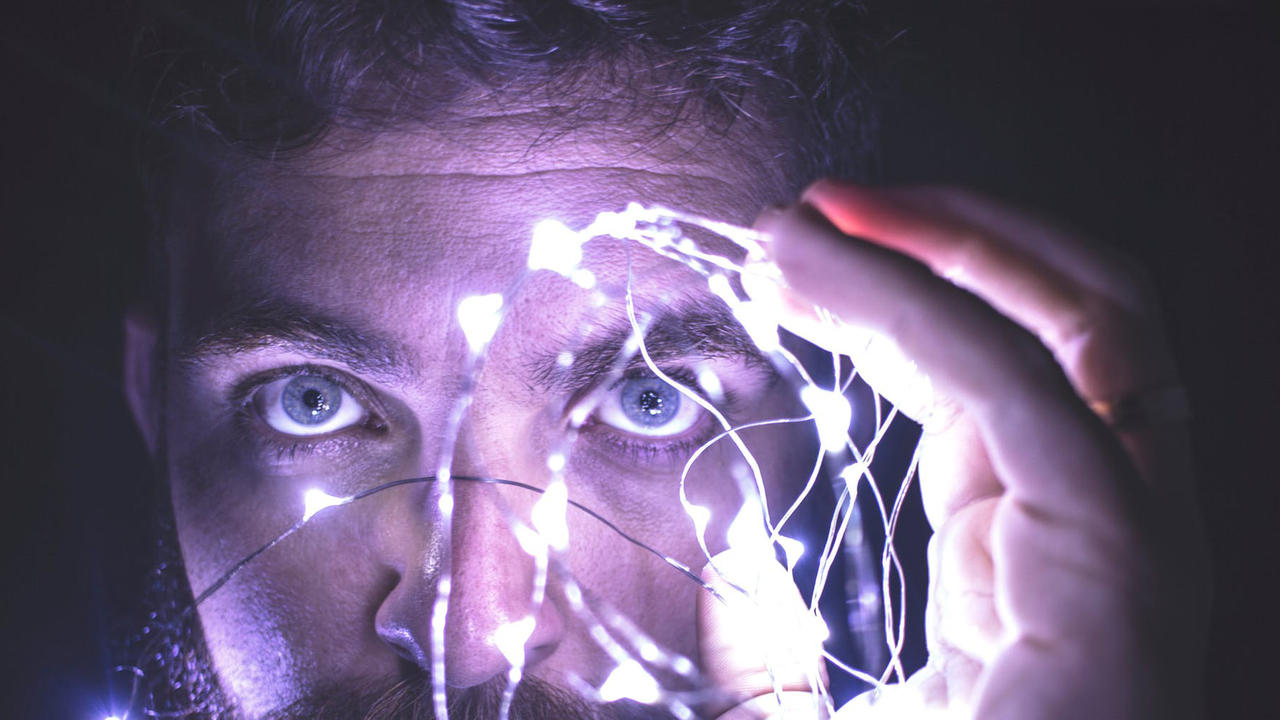Person holding lights in front of face