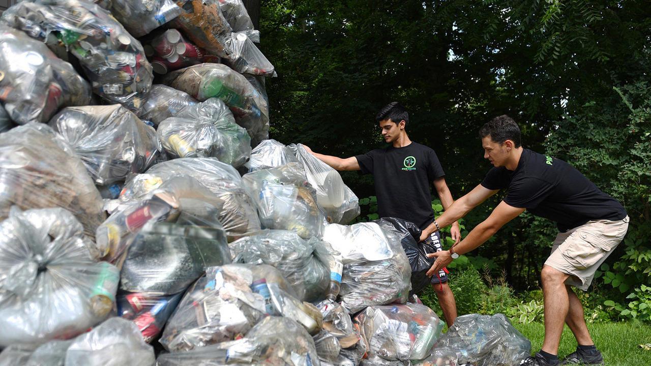 Pickwaste founders next to garbage bags