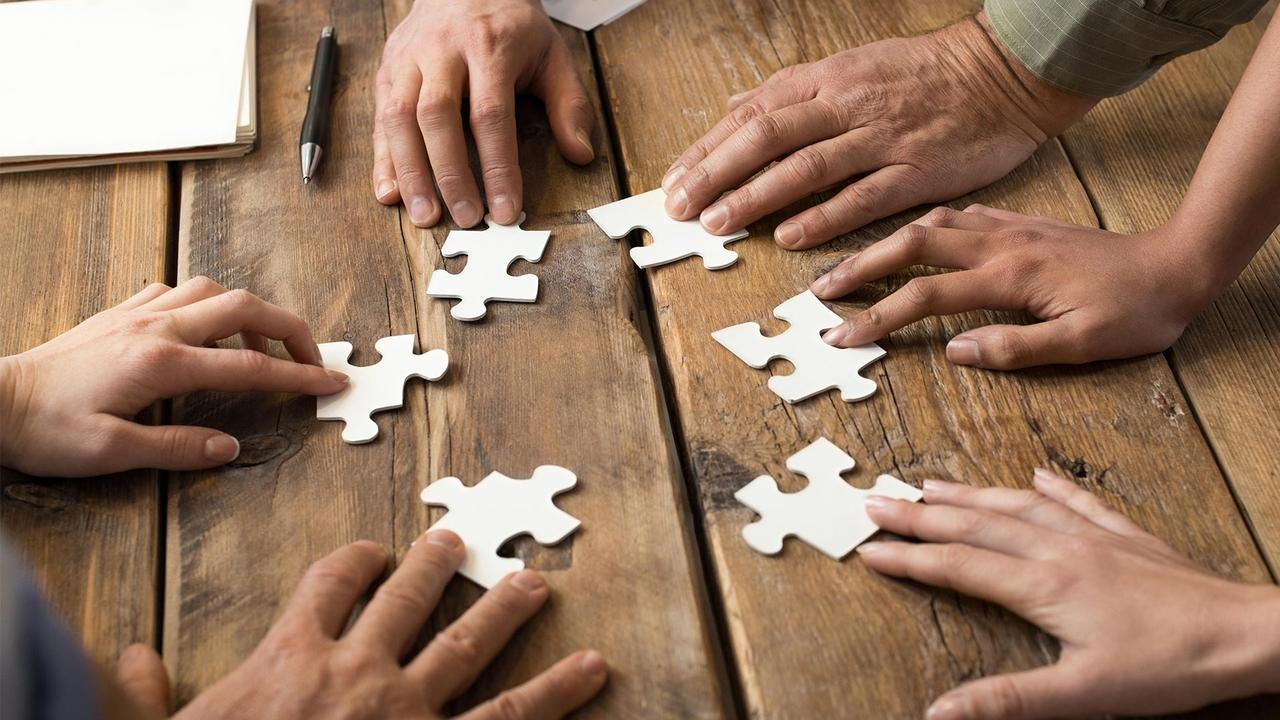 Hands on jigsaw puzzle pieces on a table