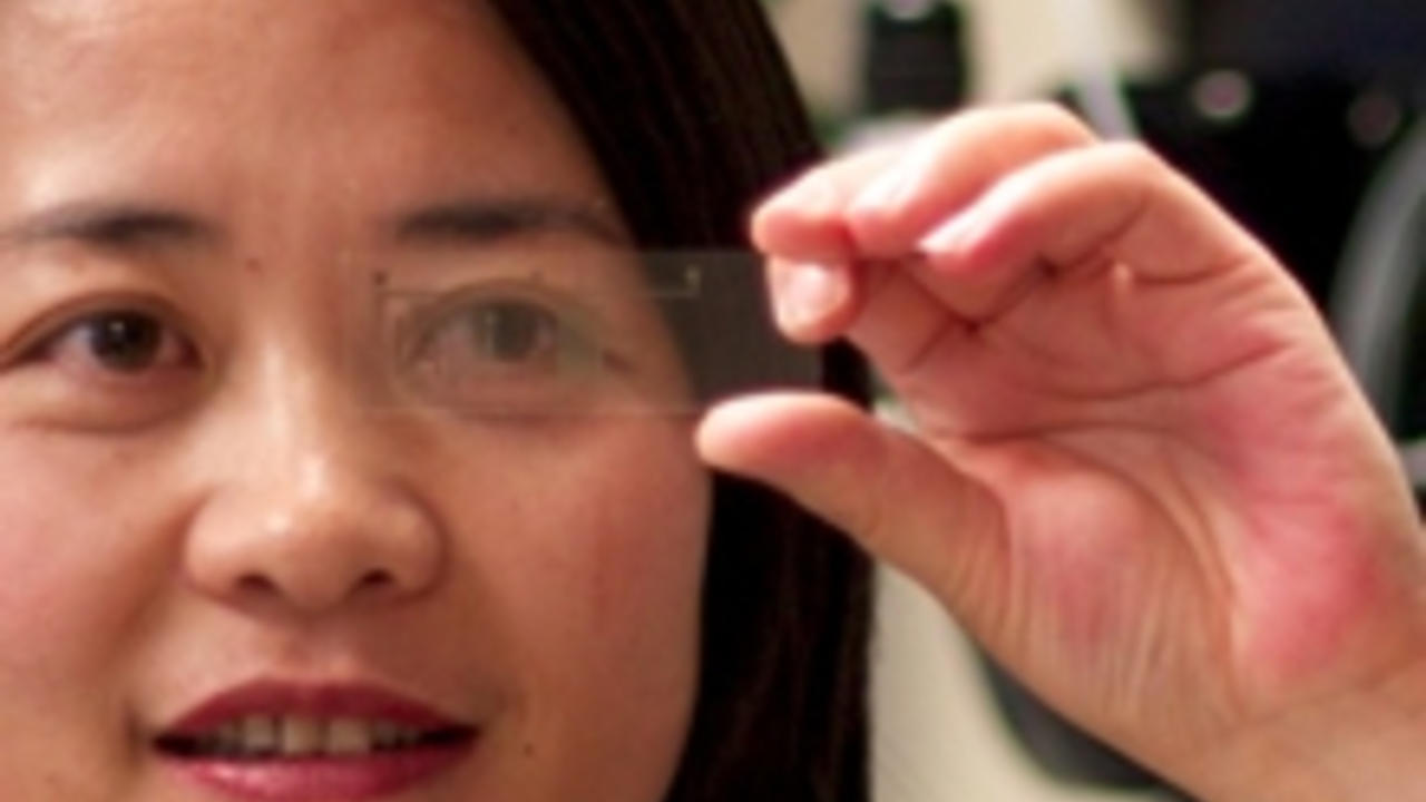 Woman looking through a transparent, microscope slide like lab on a chip.