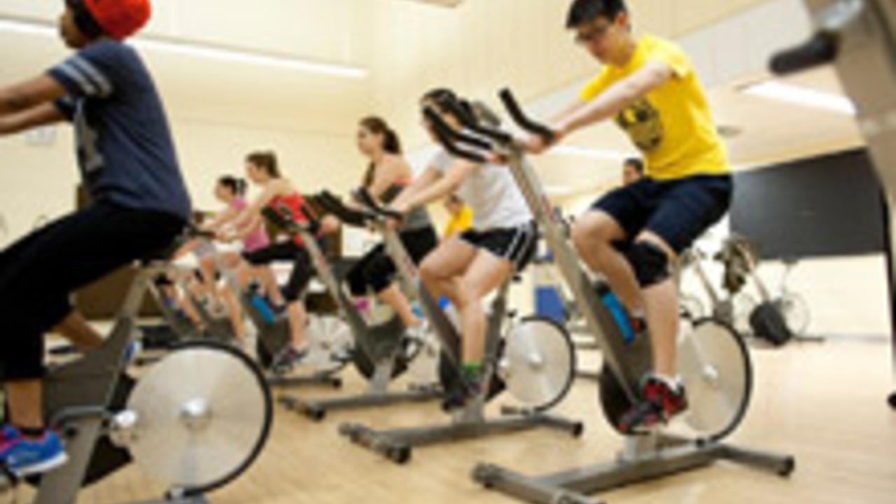 David Huang participating in a spin class on campus