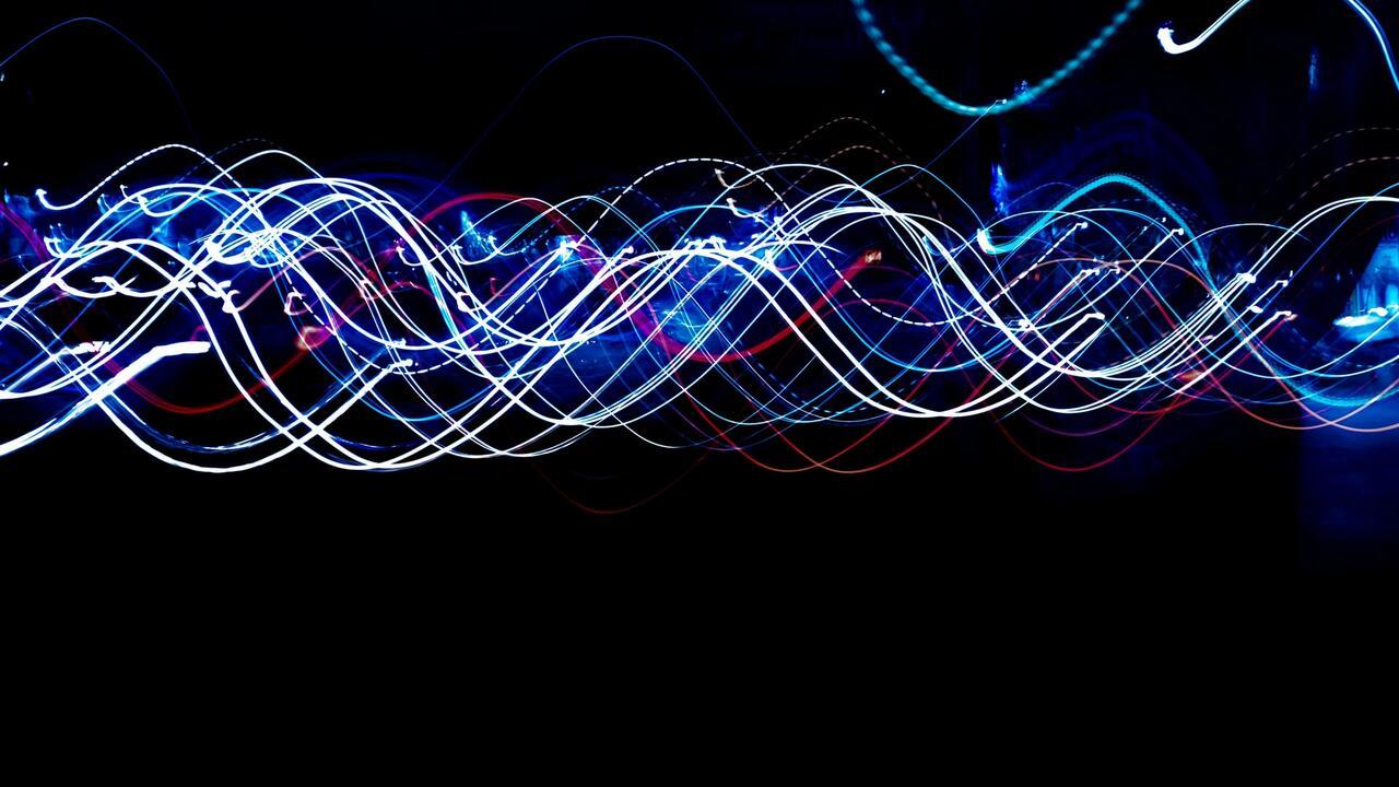 wavering coloured lines across dark background