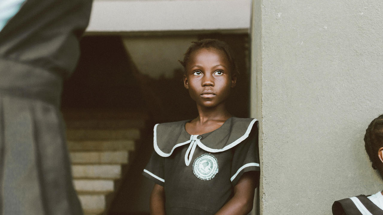 African girl standing in her school uniform