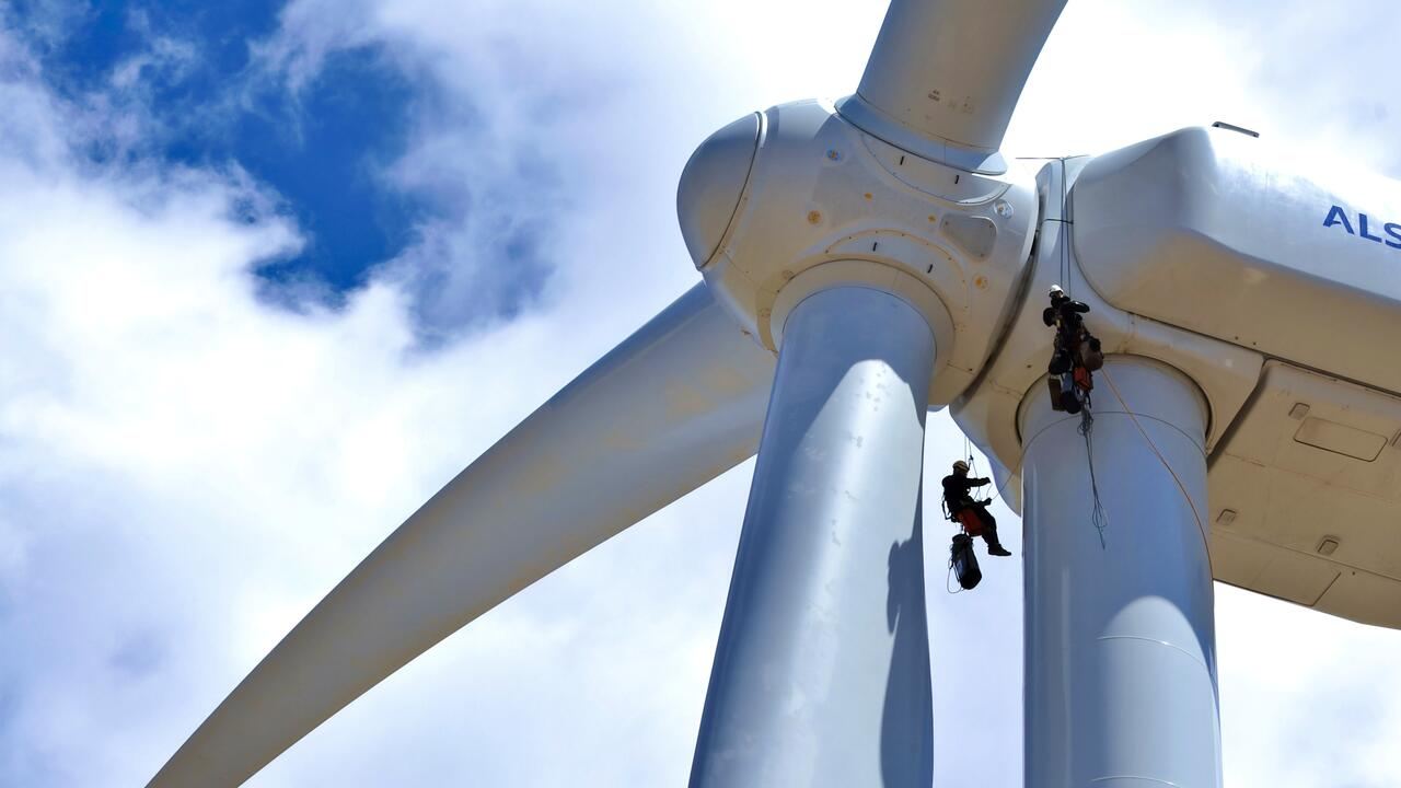 wind turbine with two workers on rigging