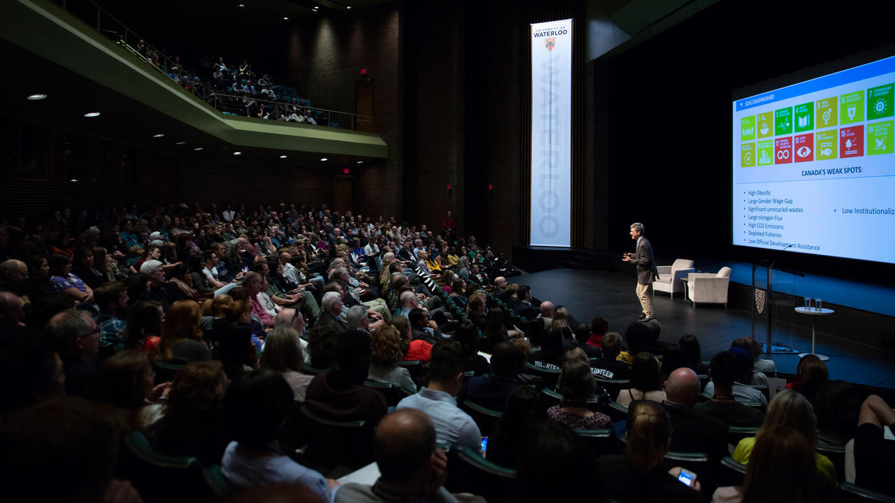 A large crowd of people gather in an auditorium