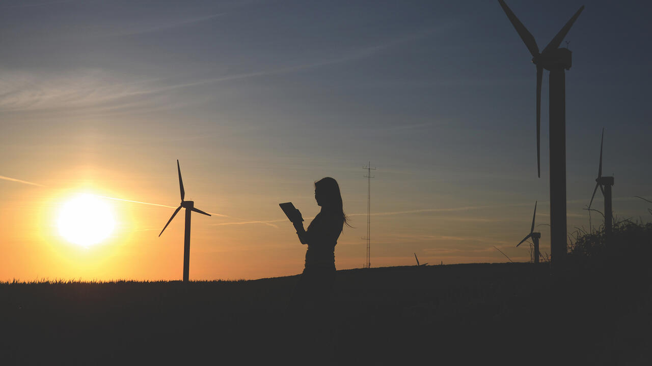 Someone reading with windmills and the sun in the background