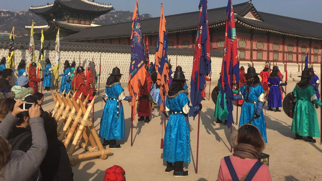 A photo taken in South Korea of people standing in bright coloured robe holding large flags.