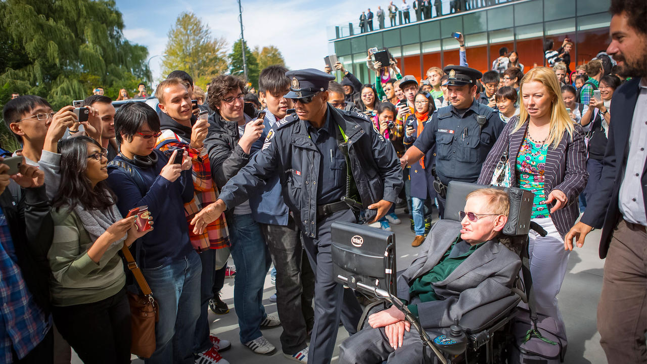 Stephen Hawking being greeted by crowds in 2012.
