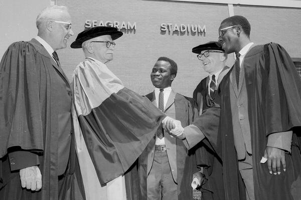 Two Black men interacting with three white men in convocation robes
