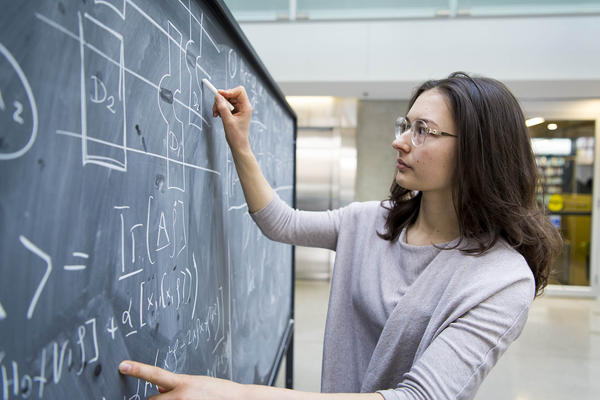 Anna writing on a blackboard