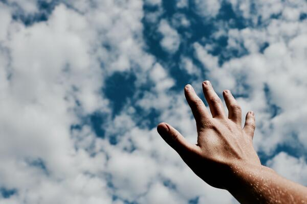 Hand raising up to a blue, cloudy sky