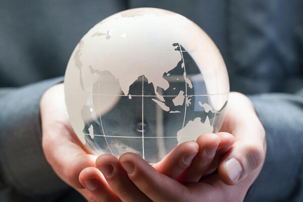 Transparent globe held by hands