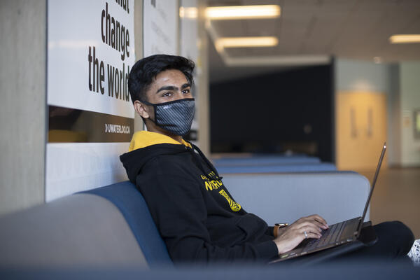 A student sitting in a Waterloo hoodie and mask while typing on a laptop