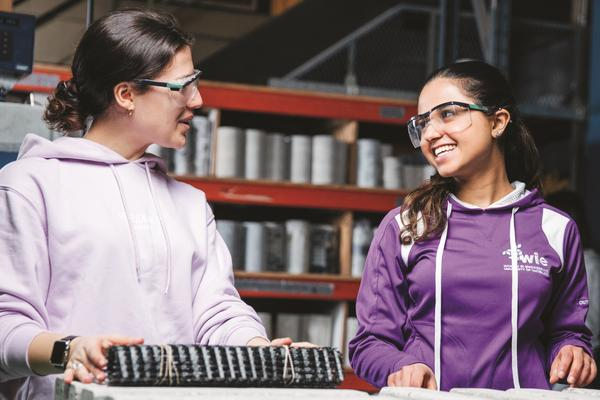 Two female students smiling at each other with goggles on at a lab